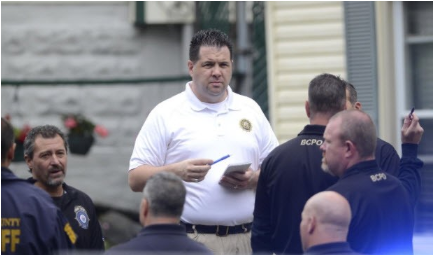 Man in White Polo Shirt Talking to Police Officers